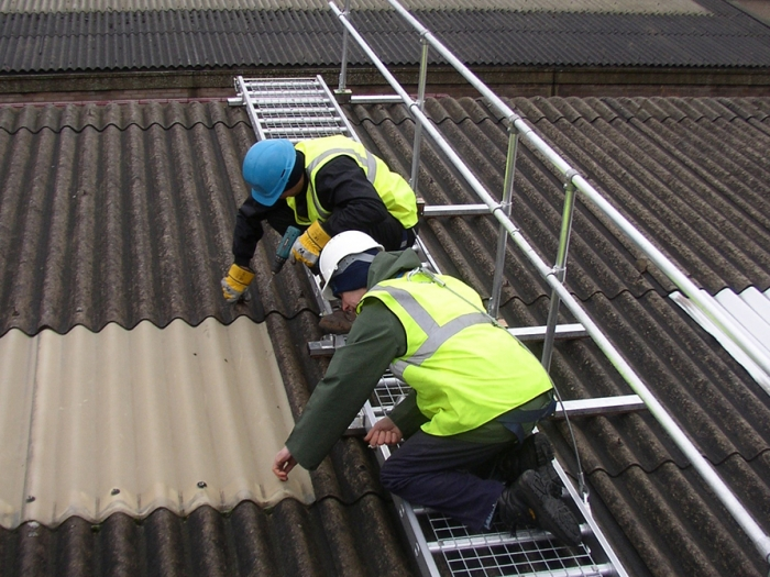 Two workers in hi-vis clothing and PPE working on a fragile roof. They are using an appropriate roof access system and safety harnesses